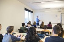 Школьников, слушая учителя в классе — стоковое фото