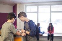 Schoolchildren talking in corridor — Stock Photo