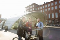 Men with bicycle talking — Stock Photo