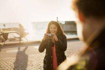 Молодая женщина фотографирует друга — стоковое фото