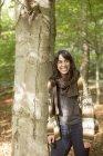 Mulher apoiando-se na árvore na floresta — Fotografia de Stock
