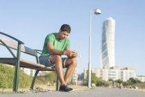 Молодий чоловік, які сидять на лавці — стокове фото