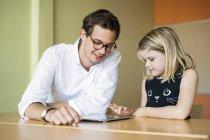 Hombre profesor viendo chica pintura - foto de stock