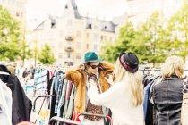 Friend helping man in wearing jacket — Stock Photo