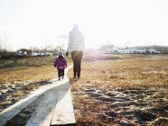 Mother with daughter walking on field — Stock Photo