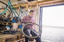 Repairman holding bicycle — Stock Photo