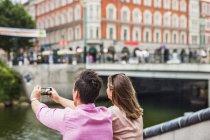Человек, стоящий рядом с другом и фотографирующий здания — стоковое фото