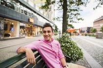 Усміхнений чоловік, сидячи на лавці автомобільним транспортом — стокове фото