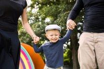 Мать и отец держат счастливого сына — стоковое фото