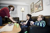 Caregiver showing laptop to people — Stock Photo