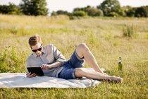 Jeune homme à l'aide de tablette numérique — Photo de stock