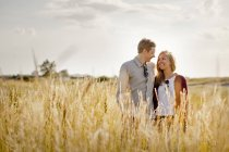 Coppia sorridente in piedi sul campo erboso — Foto stock