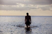 Young man walking in sea — Stock Photo