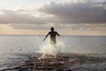 Young man running in sea — Stock Photo