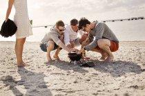 Молодые друзья зажигают барбекю — стоковое фото