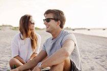 Uomo che si siede da amica alla spiaggia — Foto stock
