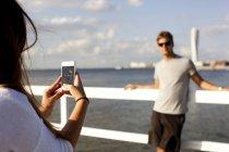 Femme photographier copain par jetée — Photo de stock