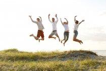 Юные друзья прыжки на пляже — стоковое фото