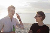 Мужчины, друзья говорят на пляже — стоковое фото