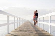 Jeune couple s'embrassant sur la jetée — Photo de stock