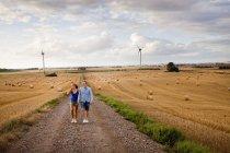 Couple marchant sur la route de terre par champ — Photo de stock