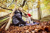 Chica mirando a la madre mientras disfruta de picnic - foto de stock