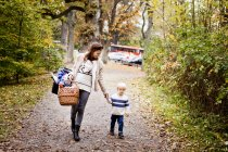 Mujer con cesta mientras camina con el niño - foto de stock