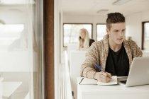 Man writing while using laptop — Stock Photo