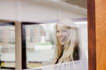 Woman in creative office seen through window — Fotografia de Stock