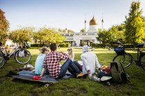 Group of friends sitting at park — Stock Photo