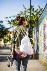 Femme avec planche à roulettes et sac à main — Photo de stock