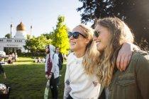 Woman standing arm around friend — Stock Photo