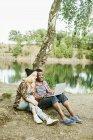 Пара с помощью ноутбука на берегу озера — стоковое фото