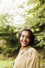 Femme souriante tout en regardant loin dans la forêt — Photo de stock