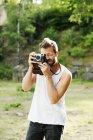 Мужчина фотографирует старомодным фотоаппаратом — стоковое фото