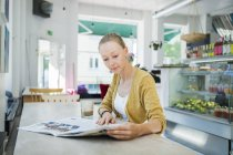 Woman reading newspaper at table — Stock Photo