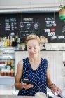 Женщина, использующая смартфон в кафе — стоковое фото