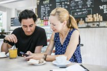 Friends using smartphone at table — Stock Photo