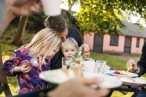 Glückliche Familie sitzt am Tisch — Stockfoto
