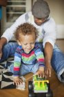 Father and son playing with toy car — Stock Photo