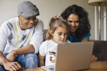 Father and mother with daughter using laptop — Stock Photo