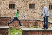 Мальчик прыгает за подпорной стены — стоковое фото