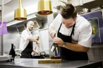 Male chef caramelizing creme brulee — Stock Photo