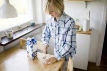 Erhöhte Ansicht des jungen Glas auf Tisch in Wohngebäude Milch einrühren — Stockfoto