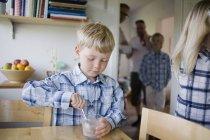 Garçon cuillère à remuer en verre sur la table à la maison avec la famille en arrière-plan — Photo de stock
