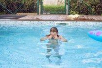 Девушка в бассейне на заднем дворе — стоковое фото