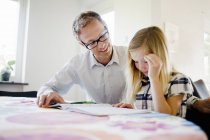 Mature father assisting daughter in homework at home — Stock Photo