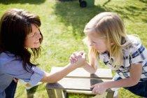 Высокий угол зрения матери и дочери армрестлинг на столе на заднем дворе — стоковое фото