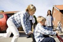 Vista lateral do menino empurrando o irmão em quadriciclo na rua — Fotografia de Stock