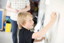 Boy writing on whiteboard — Stock Photo